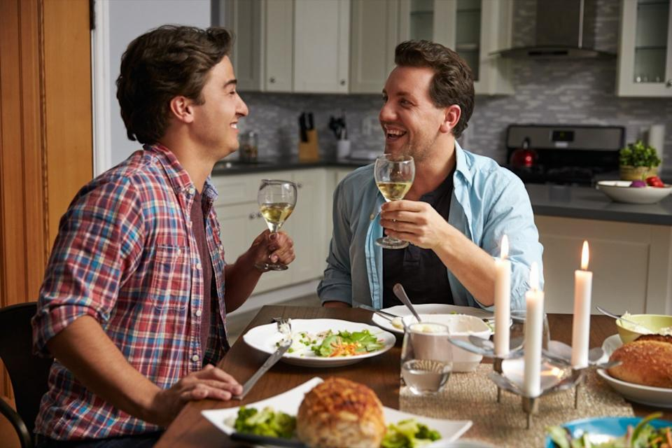 Two men having a romantic dinner and toasting each other