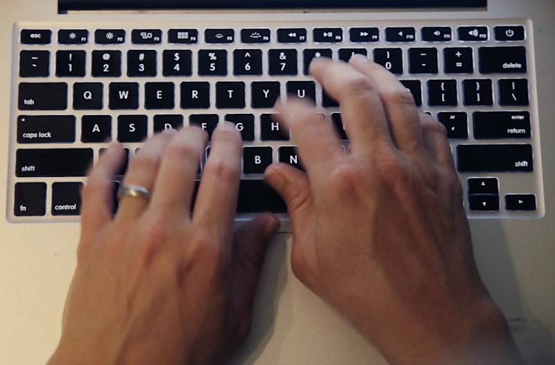 Fingers type on a laptop keyboard Monday, June 19, 2017, in North Andover, Mass. (AP Photo/Elise Amendola)