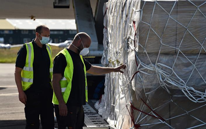 Workers unload a shipment of 120,000 surgical coveralls from China for NHS workers - GETTY IMAGES