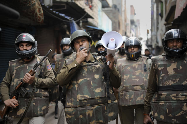A Delhi police officer makes announcements to warn residents from venturing outside their homes as Indian security officers patrol a street in New Delhi, India, Wednesday, Feb. 26, 2020. At least 20 people were killed in three days of clashes in New Delhi, with the death toll expected to rise as hospitals were overflowed with dozens of injured people, authorities said Wednesday. The clashes between Hindu mobs and Muslims protesting a contentious new citizenship law that fast-tracks naturalization for foreign-born religious minorities of all major faiths in South Asia except Islam escalated Tuesday. (AP Photo/Altaf Qadri)