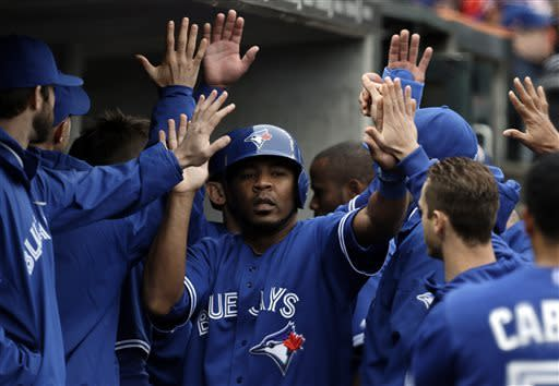 Toronto Blue Jays' Edwin Encarnacion, center, celebrates after scoring on a Mark DeRosa two-run double against the Detroit Tigers in the sixth inning of a baseball game in Detroit, Wednesday, April 10, 2013. (AP Photo/Paul Sancya)