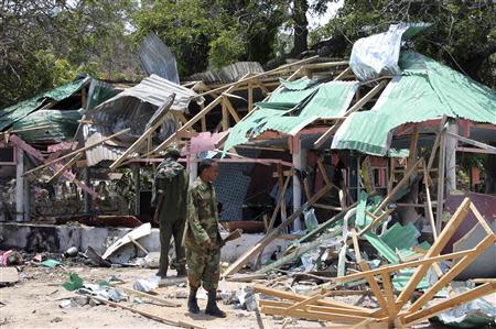 A Somali soldier stands in front of the destroyed Village Restaurant in Hamaerweyne district in Mogadishu