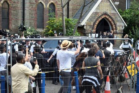 FILE PHOTO: Police officers protect the entourage carrying Britain's Prime Minister Theresa May from a crowd of people after she visited a church following the fire that destroyed The Grenfell Tower block, in north Kensington, West London, Britain June 16, 2017. REUTERS/Hannah McKay/File Photo