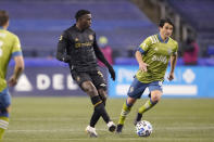 Los Angeles FC defender Jesus David Murillo, left, passes in front of Seattle Sounders midfielder Nicolas Lodeiro during the second half of an MLS playoff soccer match, Tuesday, Nov. 24, 2020, in Seattle. (AP Photo/Ted S. Warren)