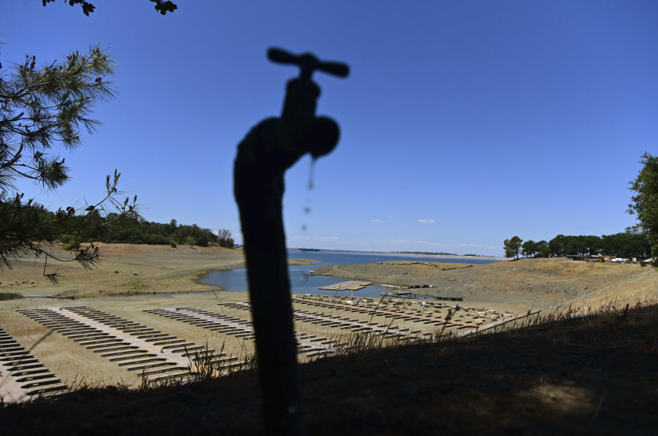 FILE - In this May 22, 2021, file photo, water drips from a faucet near boat docks sitting on dry land at the Browns Ravine Cove area of drought-stricken Folsom Lake, in Folsom, Calif. The Metropolitan Water District of Southern California declared a water supply alert for the first time in seven years and is asking residents to voluntarily conserve Tuesday, Aug. 17, 2021, hoping to lessen the need for more severe actions such as reducing water supplies to member agencies. The Metropolitan Water District of Southern California receives about half its water from the Colorado River and State Water Project. (AP Photo/Josh Edelson, File)