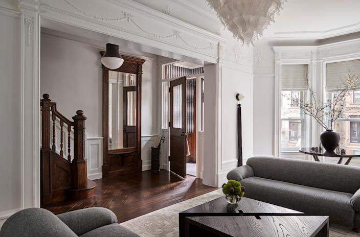 "<div class=""caption""> Gillian and Josh Dubin and their three children live in this 1903 Park Slope brownstone. The five-story, 4,600-square-foot home, which had been converted into three apartments, underwent a top-to-bottom renovation by architect <a href=""https://www.poandco.com/"" rel=""nofollow noopener"" target=""_blank"" data-ylk=""slk:Jeffery Povero"" class=""link rapid-noclick-resp"">Jeffery Povero</a>, who preserved and recreated original elements like crown moldings, plaster trims, and wall panelings. In the entrance, he expanded the opening leading to the living room. ""It really helps feature the mirror and the spectacular piece of woodwork in the staircase,"" says Povero. </div>"