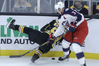 Columbus Blue Jackets defenseman Seth Jones (3) dumps Boston Bruins left wing Brad Marchand (63) to the ice as they compete for the puck in the first period of an NHL hockey game, Thursday, Jan. 2, 2020, in Boston. (AP Photo/Elise Amendola)
