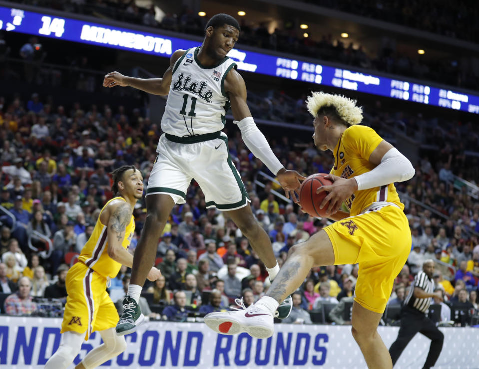 <p>Minnesota forward Jarvis Omersa, right, grabs a rebound in front of Michigan State forward Aaron Henry (11) during a second round men's college basketball game in the NCAA Tournament, Saturday, March 23, 2019, in Des Moines, Iowa. (AP Photo/Charlie Neibergall) </p>