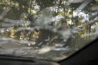 Afghan men and a boy are seen through the shattered window of a damaged car after a roadside bomb explosion in Kabul, Afghanistan, Sunday, June 6, 2021. (AP Photo/Rahmat Gul)