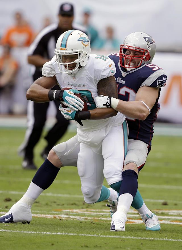 New England Patriots linebacker Dane Fletcher (52) tackles Miami Dolphins wide receiver Rishard Matthews (18) during the first half of an NFL football game, Sunday, Dec. 15, 2013, in Miami Gardens, Fla. (AP Photo/Lynne Sladky)