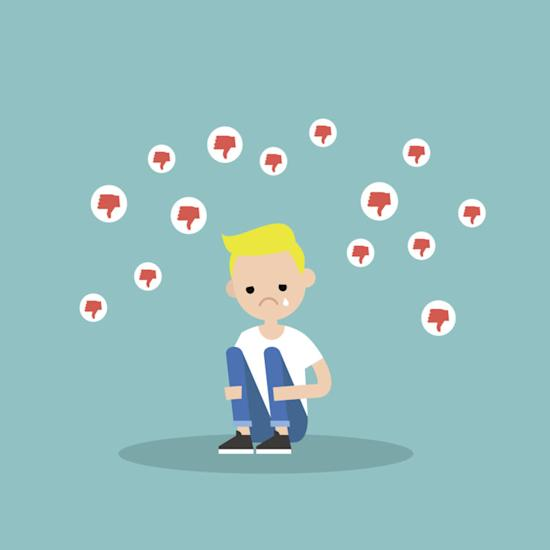 Upset crying boy sitting and hugging his knees surrounded by the dislike symbols / editable flat vector illustration, clip art