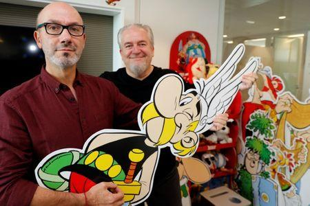 "Author Jean-Yves Ferri (L) and illustrator Didier Conrad (R) pose holding a cardboard cut-out of Asterix during an interview for their new comic album ""Asterix et la Transitalique"" (Asterix and the Chariot Race) in Vanves near Paris, France, October 17, 2017, the latest in the series created by illustrator Albert Uderzo and writer Rene Goscinny in 1959. Picture taken October 17, 2017.   REUTERS/Philippe Wojazer"