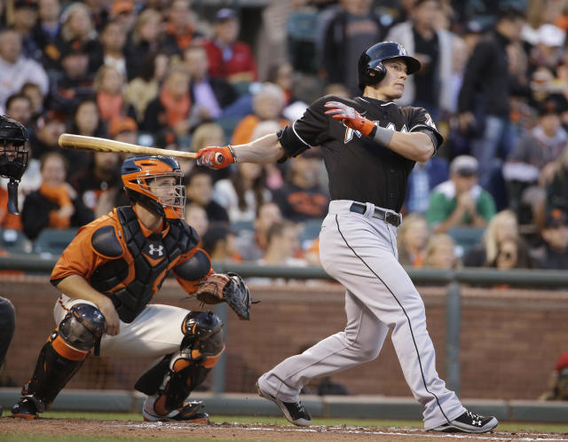 Miami Marlins' Derek Dietrich watches his two-run home run off San Francisco Giants starting pitcher Yusmeiro Petit, in front of Giants catcher Buster Posey during the third inning of a baseball game Friday, May 16, 2014, in San Francisco. (AP Photo/Eric Risberg)