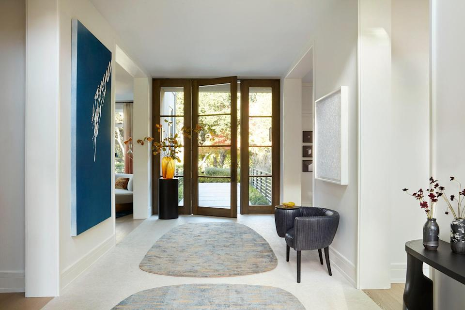 Bright and light is the theme in the entryway, which houses a large painting by Tauba Auerbach; two custom hand-knotted area rugs by Marc Phillips, a Souffle Cocktail Chair by Kelly Wearstler, Infinity Nets (ABCDQ) by Yayoi Kusama, a custom plinth by Legaspi Courts Design, and a Guaxs Vase in Amber Cubistic Glass from Table Art. The art advisor for Lau's home was Kimberly Chang Mathieu of KCM Fine Arts.