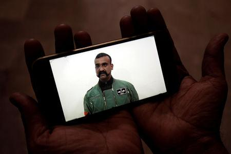 A man watches a statement of Indian Air Force pilot Abhinandan Varthaman on his mobile phone, released on Twitter by the Ministry of Information & Broadcasting, in Karachi