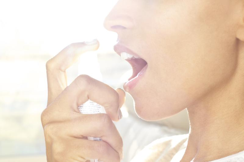 Mid adult woman spraying breath freshener in mouth.