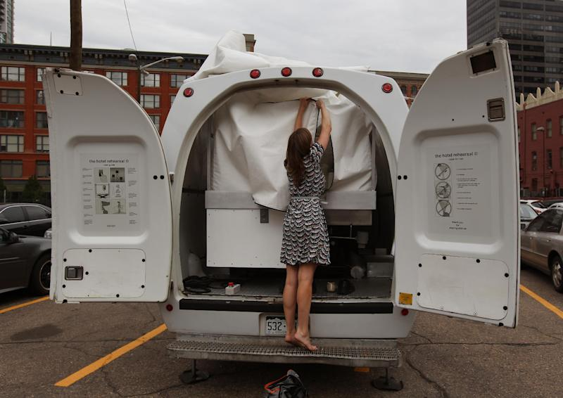 Amelia Langer, an assistant curator of Draft Urbanism, the art exhibition of the 2013 Biennial of the Americas, unzips the opening to a hotel room made of aluminum and inflated vinyl capable of being held aloft by a van-mounted scissor lift, on promotional display in a parking lot in downtown Denver, Wednesday July 25, 2013. Architectural artist Alex Schweder created the 5 by 7 foot room atop a van for the Biennial in Denver. For $50,000, a guest would get one weekend night in the puffy space, plus lots of extras including a diamond pendant and earring set, two iPod Nanos and a dance party for 100 people in a ballroom of The Curtis Hotel. (AP Photo/Brennan Linsley)