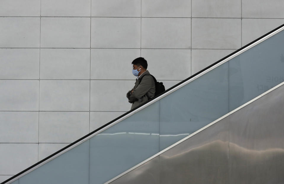 A man wearing a face mask rides the escalator in Seoul, South Korea, Wednesday, March 4, 2020. (AP Photo/Lee Jin-man)