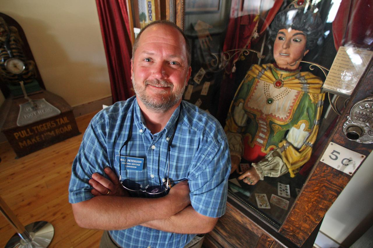 In this July 28, 2011 photo, Bill Peterson, curator of Interpretation for the Montana Heritage Commission, poses for a photo near an antique Gypsy fortune teller machine, that sat for decades in a Virginia City, Mont., restaurant and has received multimillion dollar offers from curators including magician David Copperfield. Collectors say the 100-year-old machine that speaks your fortune may be the last of its kind. (AP Photo/Michael Albans)