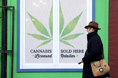 FILE PHOTO: A man walks past a sign outside the Natural Vibe store after legal recreational marijuana went on sale in St John's