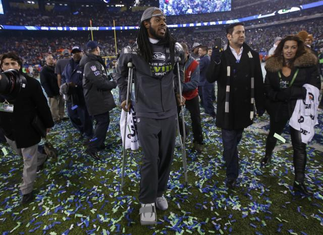 Seattle Seahawks Richard Sherman walks on crutches after the Seahawks defeated the Denver Broncos in the in the NFL Super Bowl XLVIII football game in East Rutherford, New Jersey, February 2, 2014. REUTERS/Shannon Stapleton (UNITED STATES - Tags: SPORT FOOTBALL)