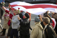 People, most of them pensioners, carry a big old Belarusian national flag during an opposition rally to protest the official presidential election results in Minsk, Belarus, Monday, Oct. 26, 2020. Factory workers, students and business owners in Belarus have started a general strike, calling for authoritarian President Alexander Lukashenko to resign after more than two months of mass protests triggered by a disputed election. (AP Photo)