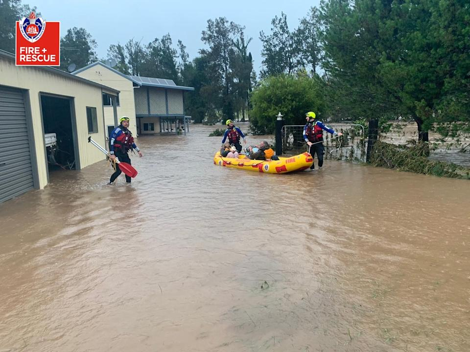 A photo of Fire and Rescue NSW crew helping residents in flood waters on the Mid North Coast.