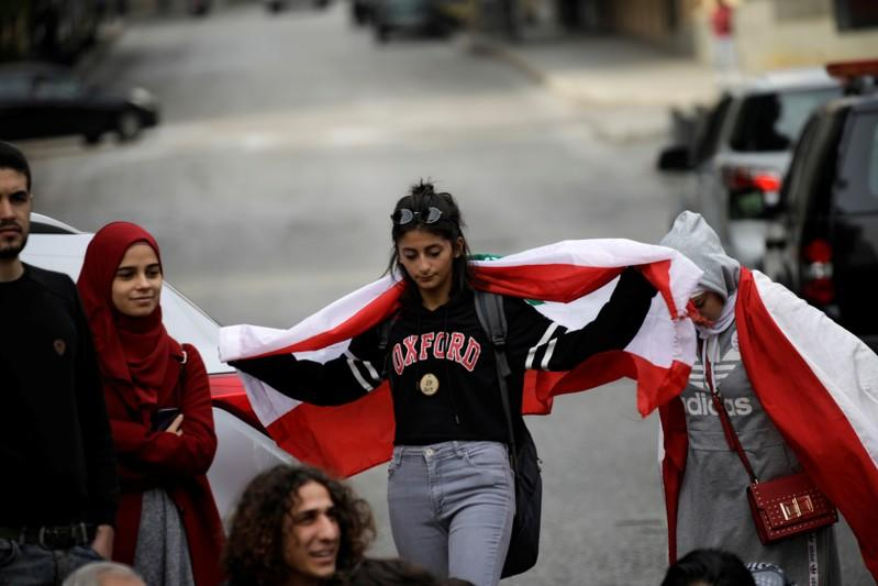 A protester holds a Lebanese flag at a roadblock during ongoing anti-government demonstrations in Beirut