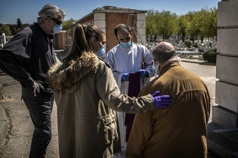 SPAIN: Family members talk to a priest before the burial of a loved one, a victim of COVID-19, at the Almudena cemetery in Madrid.