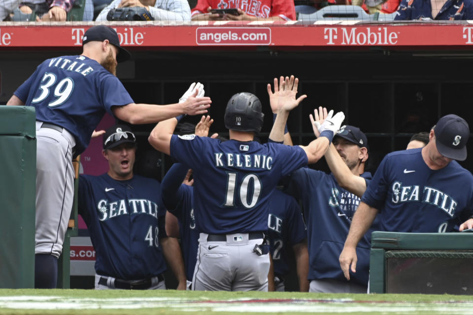 Seattle Mariners' Jarred Kelenic (10) is congratulated in the dugout after hitting a solo home run in the seventh inning of a baseball game against the Seattle Mariners, Sunday, Sept. 26, 2021, in Anaheim, Calif. (AP Photo/Michael Owen Baker)
