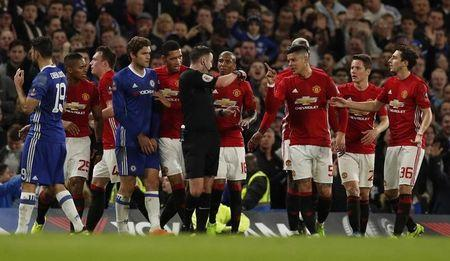Manchester United's Marcos Rojo and teammates remonstrate with referee Michael Oliver after Ander Herrera was shown a red card