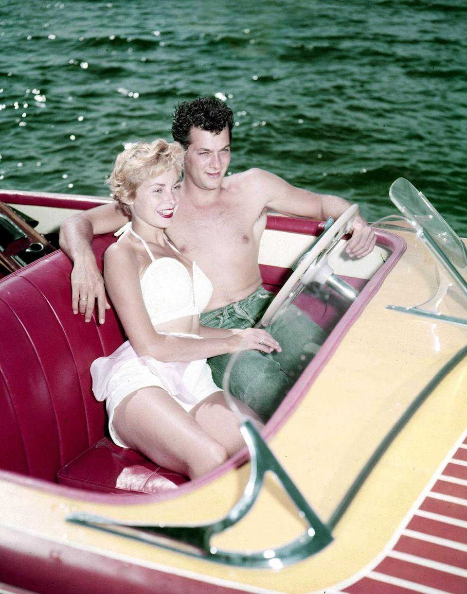 <p>Janet Leigh cozies up to her husband, Tony Curtis, in the front seat of a speed boat. Whether intentional or not, the <em>Psycho </em>actress<em>'</em>s red pout perfectly matches the interior of the vessel. </p>