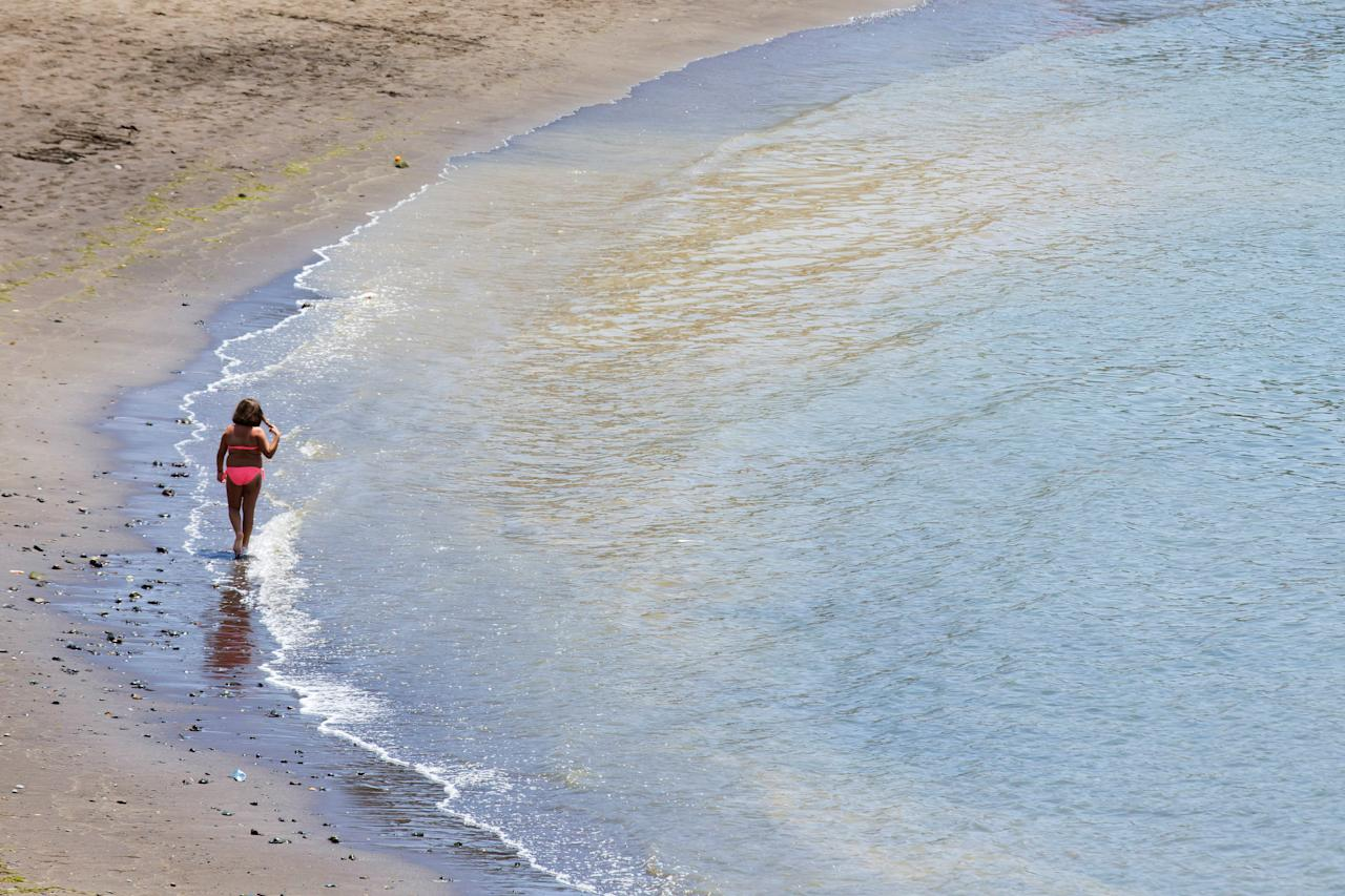"A girl walk at ""Las Maranuelas"" beach, one of the beaches where people have been warned about a micro algae invasion which can produce some health problems, in Mogan, at the Canary Island of Gran Canaria, Spain August 16, 2017. REUTERS/Borja Suarez"