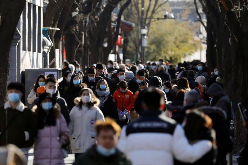 People wearing face masks following the coronavirus disease (COVID-19) outbreak walk along Nanluoguxiang alley