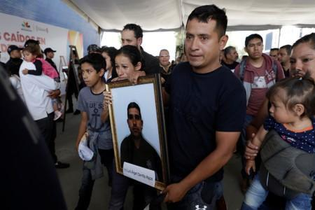 Relatives of a police officer, who was killed along other fellow police officers during an ambush by suspected cartel hitmen, carry his framed photo during an homage organised by the state government, in Morelia