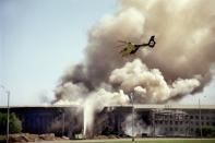FILE - A helicopter flies over the Pentagon in Washington as smoke billows over the building on Sept. 11, 2001, after a hijacked airliner crashed into the west side of the building, killing 184 people. Most Americans were guided through the events of the day by one of three men: Tom Brokaw of NBC News, Peter Jennings of ABC and Dan Rather of CBS. Each had extensive reporting experience before that, Brokaw and Rather were at the White House during Watergate, and Jennings has been a foreign correspondent. (AP Photo/Heesoon Yim, File)