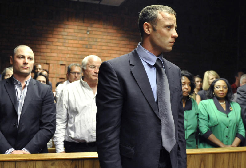 Olympian Oscar Pistorius, foreground, stands following his bail hearing, as his brother Carl, left, and father Henke, second from left, look on in Pretoria, South Africa, Tuesday, Feb. 19, 2013. Pistorius fired into the door of a small bathroom where his girlfriend was cowering after a shouting match on Valentine's Day, hitting her three times, a South African prosecutor said Tuesday as he charged the sports icon with premeditated murder. The magistrate ruled that Pistorius faces the harshest bail requirements available in South African law. (AP Photo)