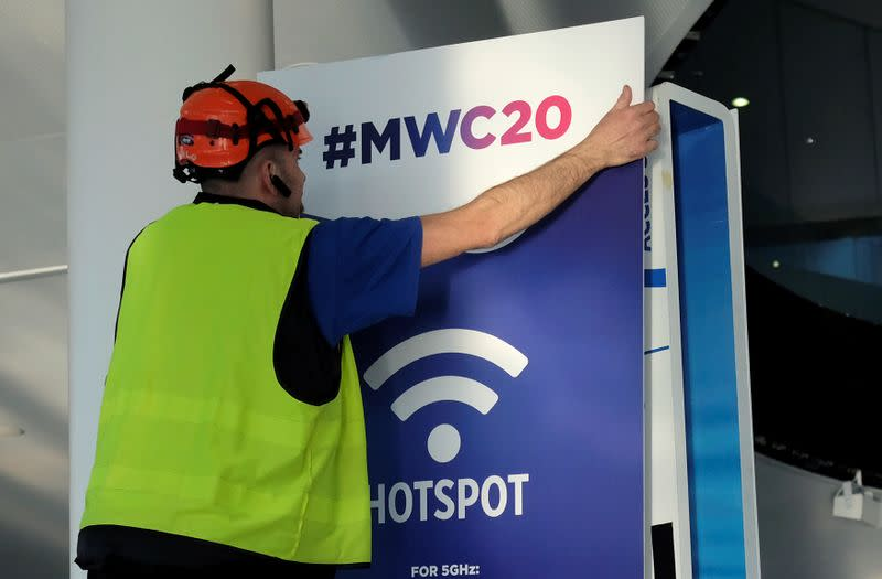 An employee places a banner with information of MWC20 in Barcelona