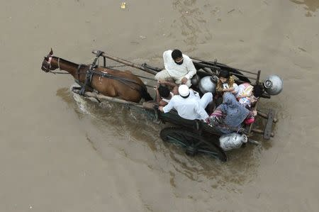 A Pakistani family travels on a horse-cart through flood road following heavy rain in Lahore September 4, 2014. REUTERS/Mohsin Raza