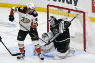 Los Angeles Kings goaltender Calvin Petersen, right, stops a shot behind Anaheim Ducks left wing Max Comtois (53) during the first period of an NHL hockey game Tuesday, April 20, 2021, in Los Angeles. (AP Photo/Marcio Jose Sanchez)