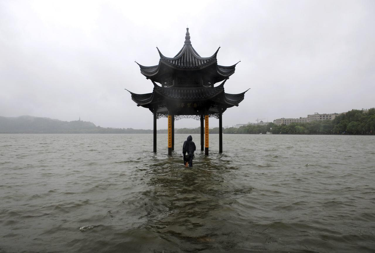 RNPS - PICTURES OF THE YEAR 2013 - A man walks towards a flooded pavilion by the overflowing West Lake after Typhoon Fitow hit Hangzhou, Zhejiang province October 8, 2013. Four people were killed and hundreds of thousands evacuated after Typhoon Fitow hit eastern China, destroying houses and farmlands and closing ports and airports. REUTERS/Lang Lang (CHINA - Tags: SOCIETY ENVIRONMENT TPX)