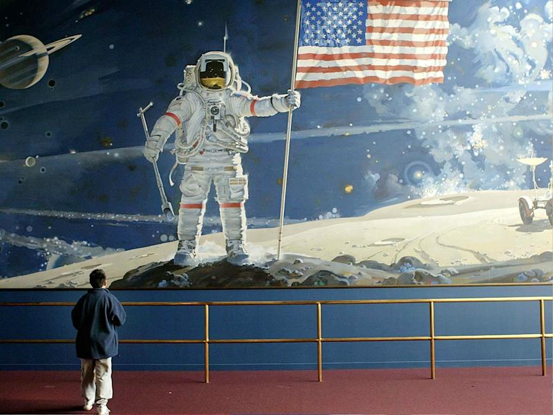 A boy looks at a wall-sized mural depicting an astronaut walking on the moon at the Smithsonian Air and Space Museum in Washington DC: Mark Wilson/Getty Images