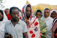 Men stand in line to receive food donations, at the Tsehaye primary school, in Shire