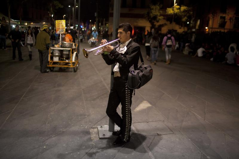 In this Oct. 5, 2012 photo photo, professor at the Mariachi School Ollin Yoliztli, Eduardo Sanchez Ortiz, practices as he waits for clients at Plaza Garibaldi in Mexico City. The new mariachi school in Mexico City is seeking to revive a music that's lost ground over the years. The school, whose name means life and movement in indigenous Nahautl, teaches folk bands how to play professionally while grooming a new generation of songwriters and composers. (AP Photo/Alexandre Meneghini)