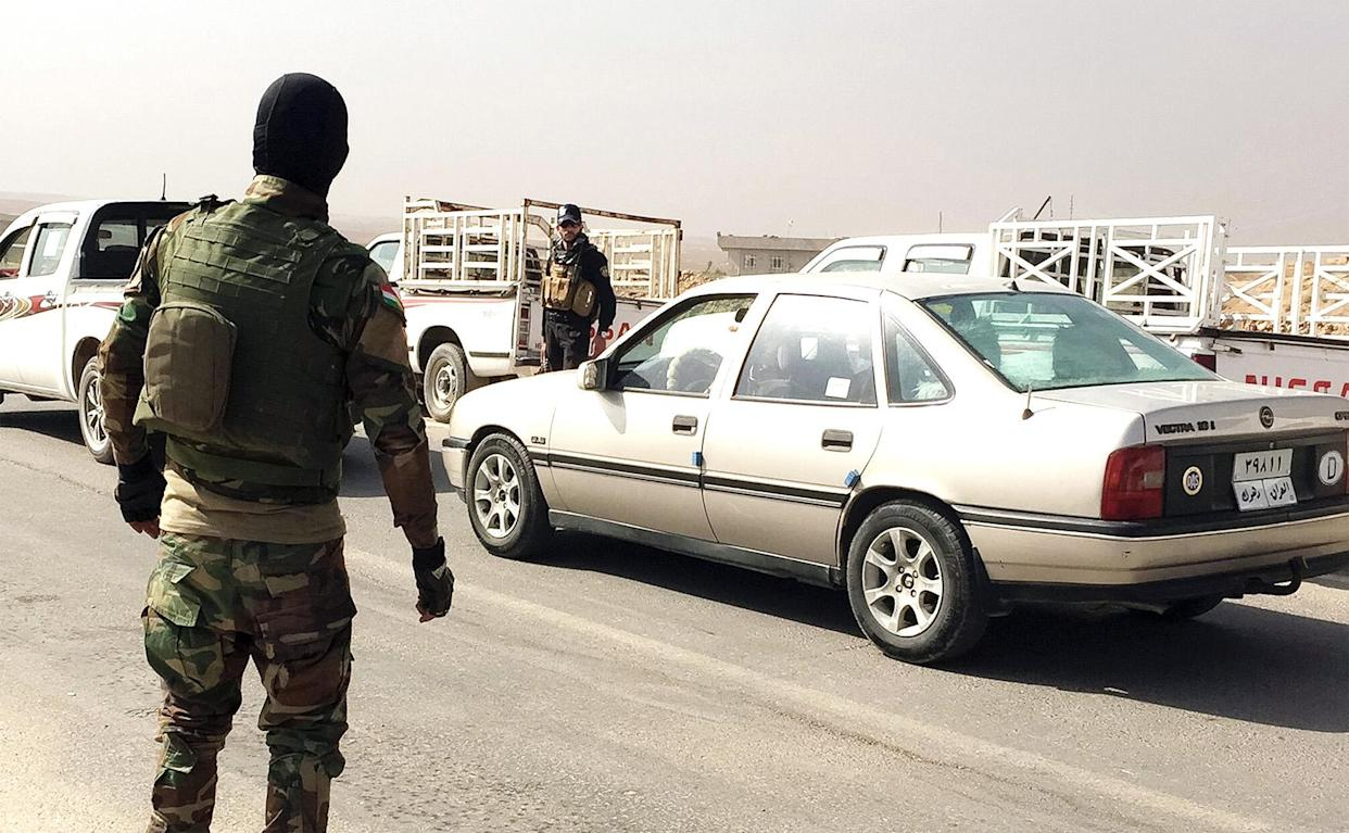 Achmed, left directs traffic at last checkpoint before Narawan encampment. His fiance and friends are in Mosul, and hopes to one day go to America. (Photo: Ash Gallagher for Yahoo News)