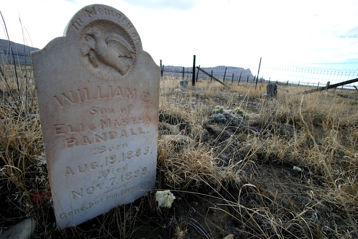 The headstone of 14-year-old William E. Randall stands in the Woodside Cemetery on July 27, 2012 in Woodside, Utah. The family that owns the 700-acre townsite has put it up for sale. They are seeking $3.9 million. Woodside once bustled with about 300 residents in the early 1900s when it was a water stop for steam engines. Now the town sits empty. (AP Photo/The Deseret News, Geoff Liesik) SALT LAKE TRIBUNE OUT; PROVO DAILY HERALD OUT; MAGS OUT