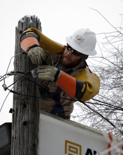 Cory Bean works atop a utility pole to repair a power line, Thursday, Dec. 26, 2013, in East Lansing, Mich. Bean is part of a crew from utility service company T&D Solutions out of Kentucky brought in to assist Consumers Energy with restoring power in Michigan after an ice storm. Bean has been working in Michigan since Sunday. (AP Photo/Al Goldis)