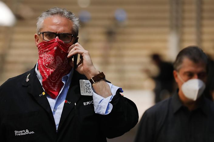 NEW YORK, NEW YORK - MAY 26: A trader walks by the New York Stock Exchange (NYSE) on the first day that traders are allowed back onto the historic floor of the exchange on May 26, 2020 in New York City. While only a small number of traders will be returning at this time, those that do will have to take temperature checks and wear face masks at all times while on the floor. The Dow rose over 600 points in morning trading as investors see economic activity in America picking up (Photo by Spencer Platt/Getty Images)