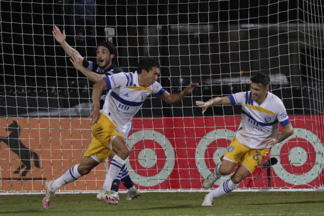 San Jose Earthquakes midfielder Shea Salinas, left foreground, celebrates his go-ahead and game-winning goal with defender Paul Marie as Vancouver Whitecaps midfielder Patrick Metcalfe reacts behind him during the second half of an MLS soccer match, Wednesday, July 15, 2020, in Kissimmee, Fla. (AP Photo/John Raoux)