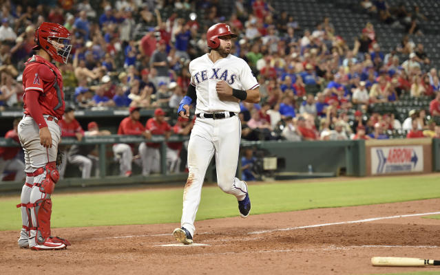 Texas Rangers' Joey Gallo scores the go-ahead run on an infield single by Rougned Odor off Los Angeles Angels relief pitcher Justin Anderson, while catcher Francisco Arcia watches during the eighth inning of a baseball game Thursday, Aug. 16, 2018, in Arlington, Texas. (AP Photo/Jeffrey McWhorter)